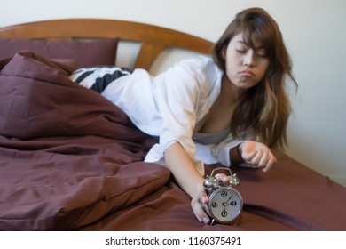 Young woman holding alarm clock on bed. wake up early in morning. Girl stop snooze alarm. female waking up sleepy and tired. woman wake up in the morning with alarm clock snooze concept.