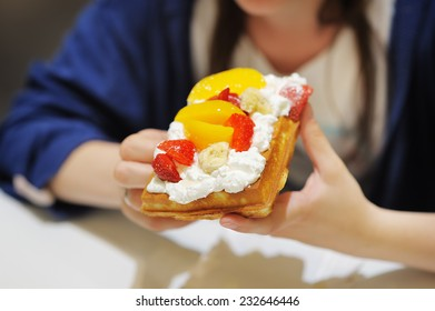 Young woman holding appetizing Belgian waffles with whipped cream and fruit