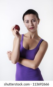 young woman holding a apple in her exercise clothes
