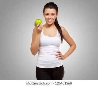 Young woman holding an apple on gray background