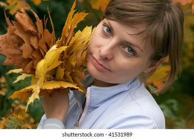 Young woman holding autumn leaves in the park