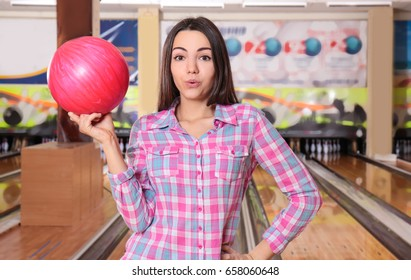 Young woman holding ball in bowling club