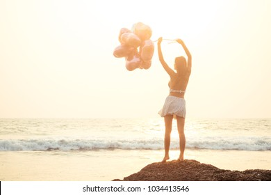 young woman holding balloons and waves at the sea view from the back