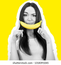 Young woman holding banana like smile near her face over yellow background. Modern fashion look.