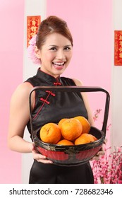 Young woman holding basket of  mandarin