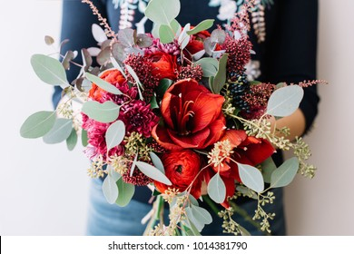 Young woman holding beautiful fresh blossoming flower bouquet in red colors