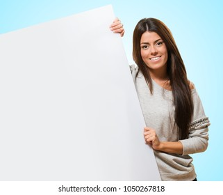 Young Woman Holding A Big Blank Card against a blue background