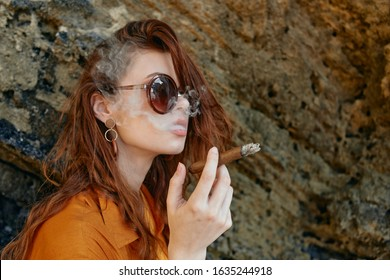 young woman holding a big cigar in her hands