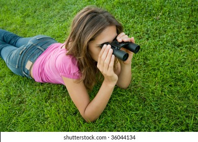 Young woman holding binocular lenses on grass