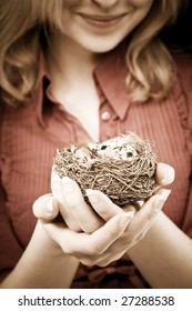 Young woman holding a bird nest in her hands. Conceptual environmental cheerful image.