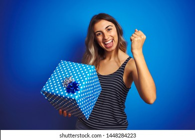 Young woman holding birthday present over blue isolated background screaming proud and celebrating victory and success very excited, cheering emotion