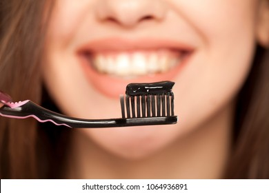 young woman holding a black tooth paste with active charcoal, and black tooth brush on white background