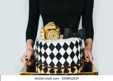Young woman holding Black and White Birthday Cake For Photographer, closeup
