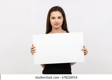 Young woman holding blank poster.Smiling woman sign board holding. Girl showing banner with copy space.