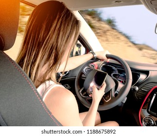 Young woman holding blank screen cell phone while driving car. Female driver hand on steering wheel & checking out her smartphone in moving vehicle. Don't text and drive concept. Close up, background.