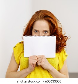 Young woman holding up a blank white spiral bound notebook in front of her mouth looking over the top at the camera with big eyes