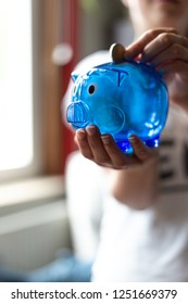 Young woman holding a blue piggy Bank in Hand, and throwing money at it