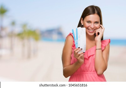 Young Woman Holding Boarding Pass at a beach