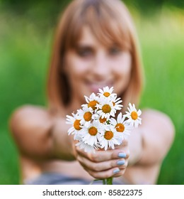 Young woman holding bouquet of camomiles.