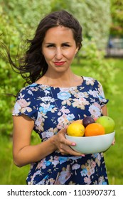 Young woman holding the bowl full of fruits