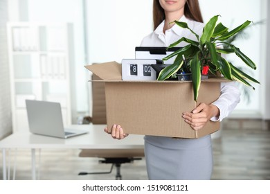 Young woman holding box with stuff at office, closeup