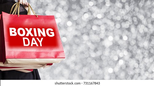 Young woman holding boxing day shopping bag on silver bokeh background