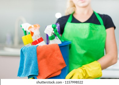 Young woman holding bucket with group of cleaning supplies for natural and environmentally friendly cleaning. Household equipment, tidying up, cleaning service concept, copy space