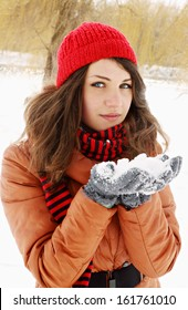 A young woman holding a bunch of snow