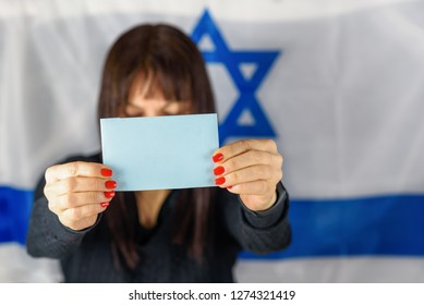 Young Woman Holding Business Card /   Ballot / Blue Voting Paper Front Of Face on Israeli Flag Background. Woman showing blank flyer brochure booklet leaflet. Space for you text, mockup.
