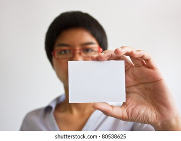 young woman holding businesscard in hand.