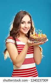 Young woman holding cake with candles on blue background