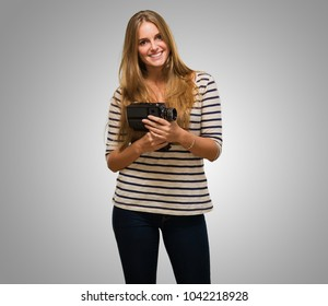 Young Woman Holding A Camera against a grey background