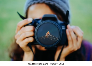 Young woman holding a camera with Himalayas mountains reflect in a front lens