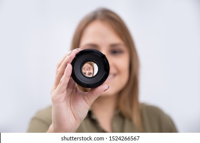 Young woman holding a camera lens in front her face isolated background