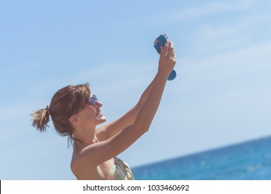 Young woman holding camera and taking photos outdoors.