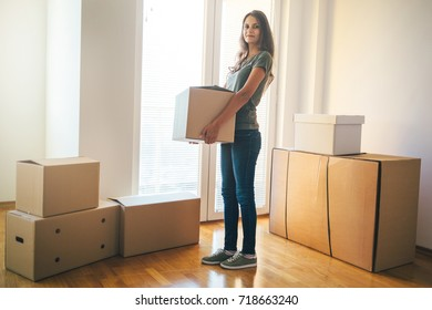 Young woman holding cardboard box. Moving into new home