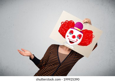 Young woman holding a cardboard with a clown on it in front of her head