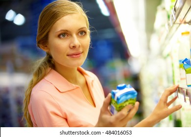 Young woman holding carton of milk in the grocery