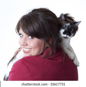 Young woman holding a cat, looking back over her shoulder; isolated on a white background.