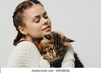 Young woman holding a cat Maine Coon hands. White background