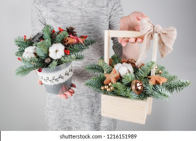 young woman holding christmas compositionin hands in light, seasonal holidays, rustic theme, adorning