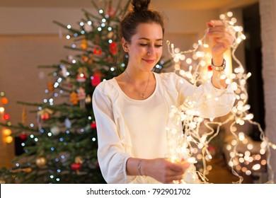 Young woman holding Christmas lights