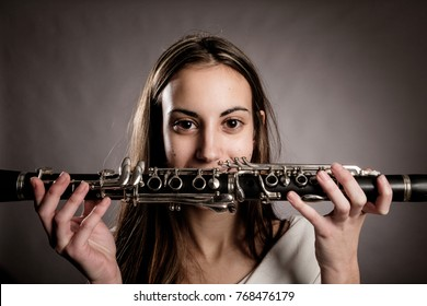 young woman holding a clarinet on a gray background