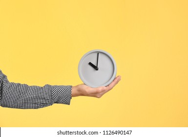 Young woman holding clock on color background. Time management