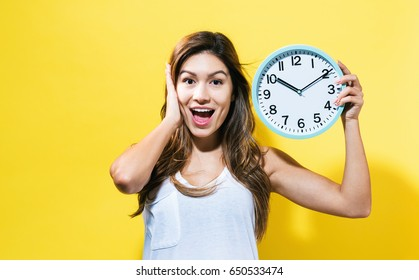 Young woman holding a clock on a yellow back ground