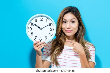 Young woman holding a clock on a blue background