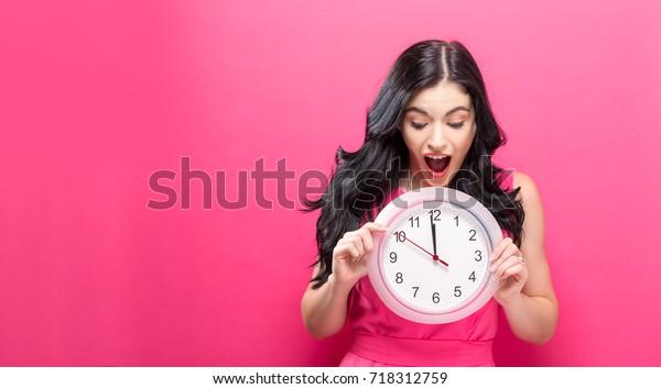 Joven sosteniendo un reloj que muestra casi 12