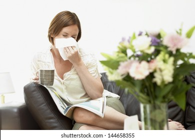 Young woman holding coffee cup and blowing nose with tissue paper on sofa
