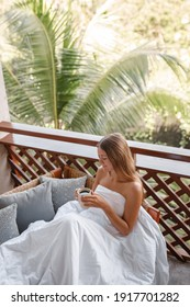 A young woman holding coffee cup while lying on sofa on balcony , looking at the cup,  green nature and palm trees background