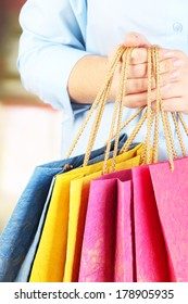 Young woman holding colorful shopping bags in  her hand, on bright background